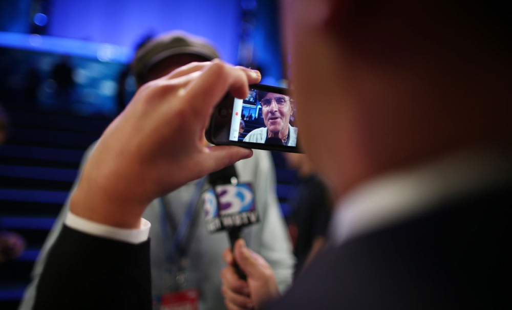 A reporter photographs musician James Taylor using an Apple iPhone as he gives an interview during the final day of the Democratic National Convention at Time Warner Cable Arena on September 6, 2012 in Charlotte, North Carolina.